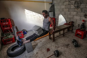 Palestinian bodybuilder Ahmed Tlatini uses breeze blocks to train at home in Gaza.