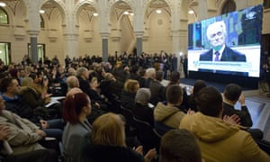 The crowd applauds as the UN court's sentencing of Radovan Karadžić is broadcast in Sarajevo city hall