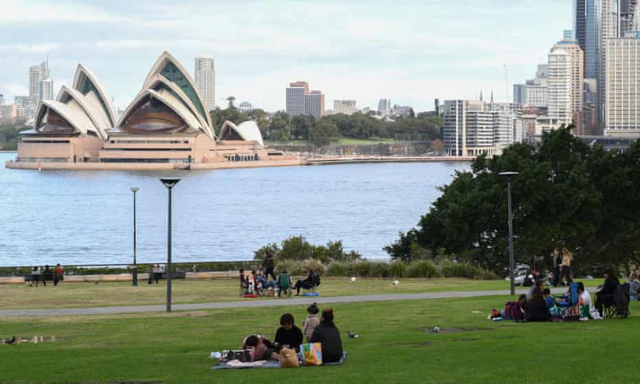 People picnicking by Sydney Harbour, with a view of the Opera House
