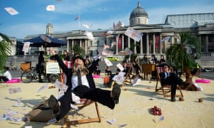 A woman throws false money into the air during a protest against tax havens, at Trafalgar square in London