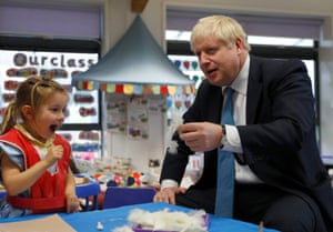 Beaconsfield, UK Boris Johnson gestures as he visits an art class with Scarlet Fickling, aged 4, at St Mary's and All Saints Primary School
