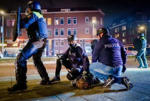Dutch policemen arrest a man during protests by a large group of young people on Beijerlandselaan in Rotterdam, on Monday night, against the introduction of a coronavirus curfew.