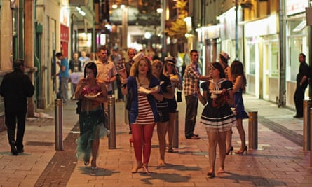 People walk between pubs and clubs in Cardiff city centre.