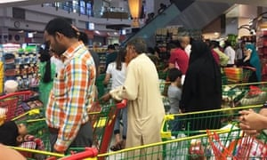 People are seen buying essential food staples at a supermarket in Doha, Qatar, as Arab nations cut ties.