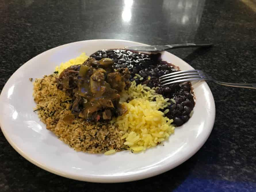Banana skin and vegetables served with tangerine sauce, beans, rice and farinha