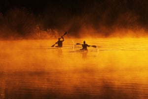 Kayakers make their way through the fog on the river Trent near Holme Pierrepont, Nottinghamshire