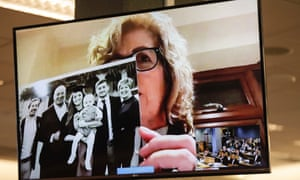 Gillian Millane, mother of murdered British backpacker Grace, holds up a photo during her victim impact statement via video link from England
