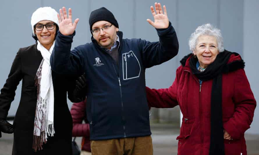 Jason Rezaian waves to media as he stands with his wife and mother after being released.
