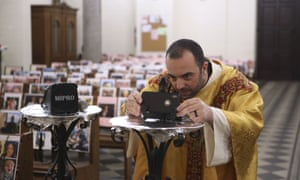 Catholic priest father Georges Nicoli adjusts a smartphone prior to celebrating a Holy Thursday mass, to be livestreamed on Facebook, with pictures of parishioners taped to the benches in the empty Notre Dame De Lourdes church in Bastia, Corsica.