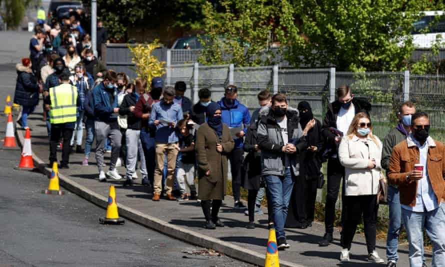People queue outside a mobile vaccine centre in Bolton on 16 May.