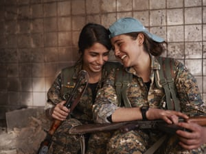 Silava and Berivan of the Yazidi Women's units (YJÊ) share a laugh in an abandoned ISIS base in Sinjar.