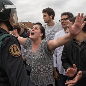 A woman protests as police move in on members of the public gathered outside to prevent them from voting in the Catalan independence referendum at a polling station in Sant Julià de Ramis