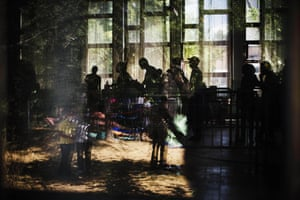 Migrants are photographed through a window as they wait for papers at an immigration centre in the southern Serbian town of Presevo. According to Amnesty International, the estimated number of people crossing the Serbia-Hungary border has increased more than 25-fold, rising from 2,370 to 60,602.