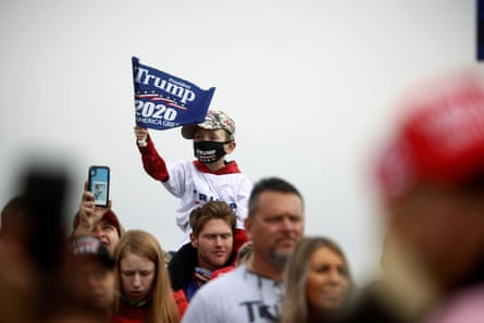 A child holds a flag as supporters wait for the rally of Donald Trump at Hickory Regional Airport in Hickory, North Carolina, on Sunday.