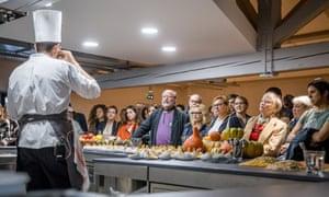 Guests listen to a chef giving a talk at Cité Internationale de la Gastronomie, Lyon, France.