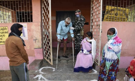 A security officer wearing a face shield as a protective measure against the coronavirus helps an elderly voter exit a polling station, during the first phase of state elections at Paliganj, in the eastern Indian state of Bihar, Wednesday, 28 October, 2020.