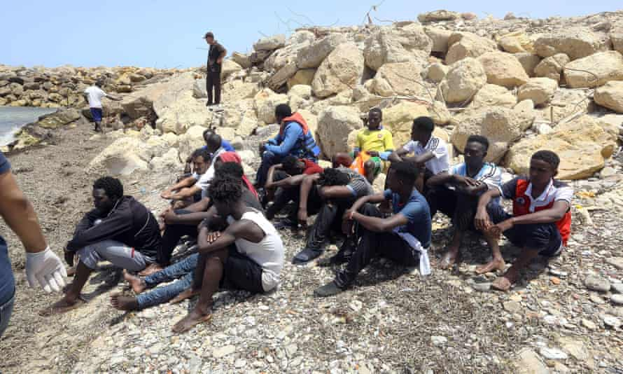 Migrants who survived the sinking of an inflatable dinghy off of the coast of Libya on the shore at al-Hmidiya.