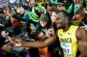Usain Bolt of Jamaica takes a selfie with fans after the men's 100m final at the London 2017 IAAF World Championships