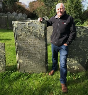 Historian Barry West stands alongside Miles Marley's grave at the St Endellion Church near Port Isaac, Cornwall.
