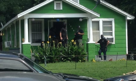Members of the Western Tennessee multi-agency gang unit (MCU) in ski masks as they execute a search on the home of Antonio Cathey's uncle, James Cathey.