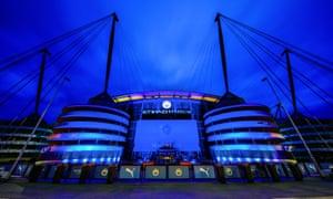 The Etihad Stadium is lit up with blue lights.
