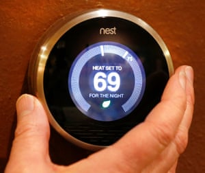 A Nest thermostat is being adjusted in a home.
