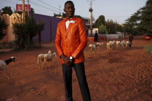 model wears an orange jacket and black trousers, standing with herd of goats passing in the background