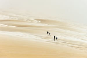 People walk on the partially snow covered Pyla sand dune after snow fall in La Teste-de-Buch, southwestern France