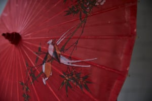 A red umbrella with a bird drawn on