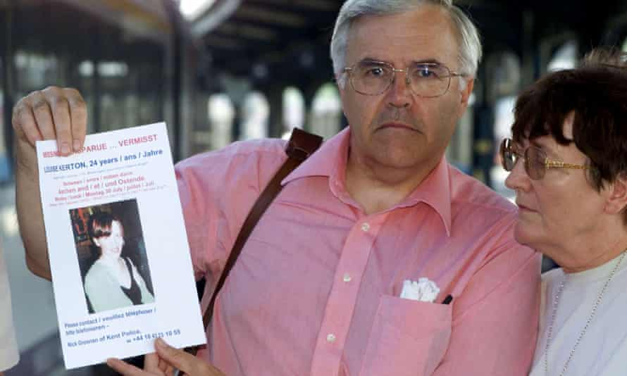 Middle-aged man and woman; he holds a missing persons flyer