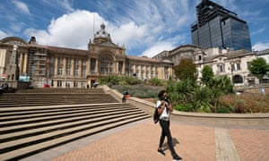 A pedestrian wearing face mask walks in the nearly empty city centre of Birmingham.