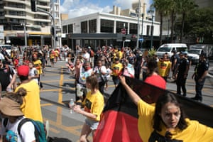 Members of the 'Stolenwealth Games' protest group march through Surfers Paradise on Saturday