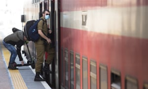 a young israeli soldier boards a train in tel aviv wearing face mask