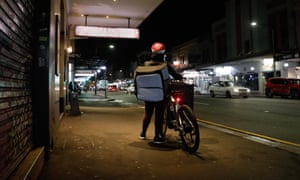 Food delivery bike rider with an insulated backpack on King Street Newtown. Sydney, Australia.  Deliveroo, menulog, food. Take away.