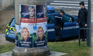 French gendarmes stand near Marine Le Pen campaign posters in Clairvaux-les-Lacs, eastern France.