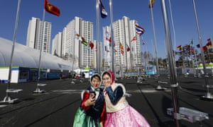 Korean girls dressed in traditional clothes take a selfie in front of the flags of competing nations at the Olympic Village in Gangneung.