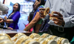 A customer inspects gold bangles at jewellery store in Mumbai, India