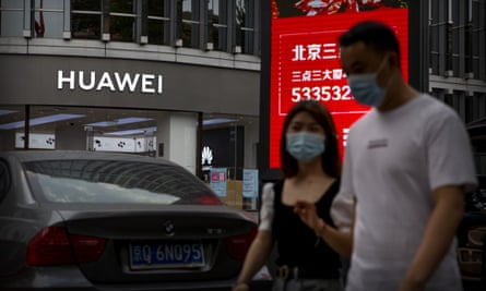 People wearing face masks walk past a Huawei store in Beijing, China