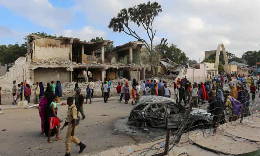 Residents gather to view the damage at the scene of a night car bomb attack in Mogadishu