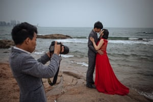 A couple pose for their pre-wedding photos in front of the Yellow Sea, in Qingdao