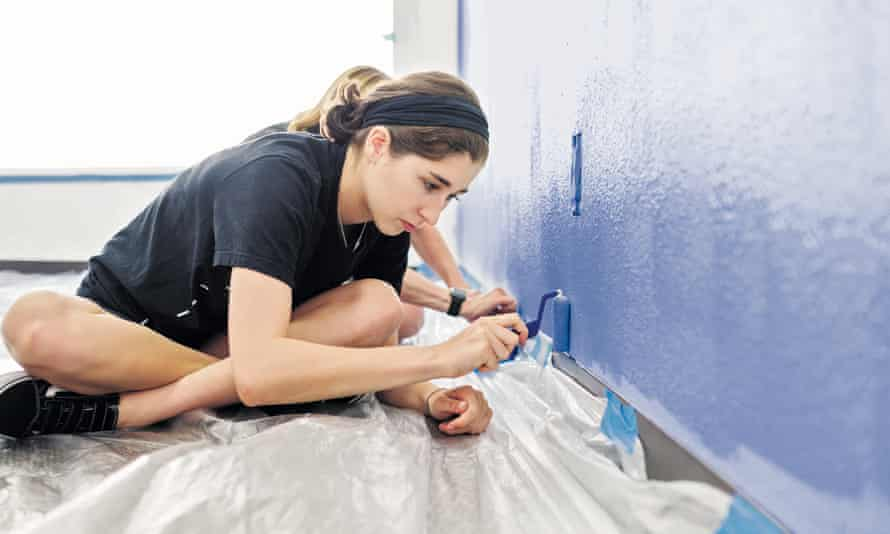 Teenager Working As A Volunteer Painting A Wall