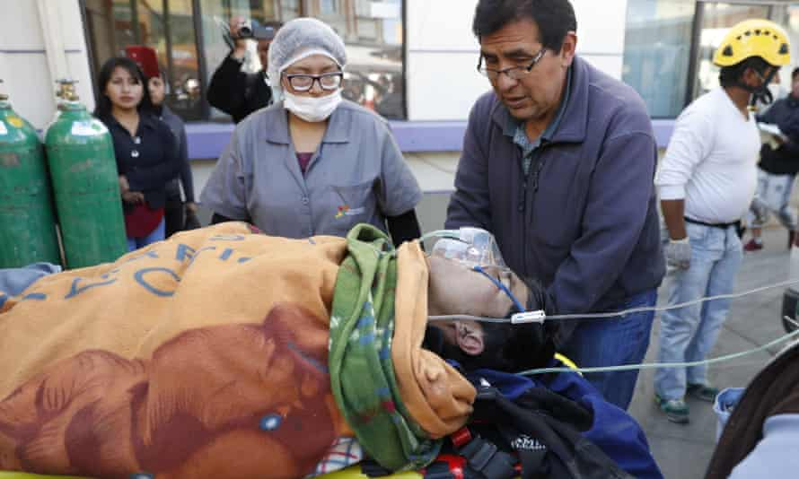 Paramedics transport a man injured during clashes with security forces to a hospital in El Alto on Tuesday.