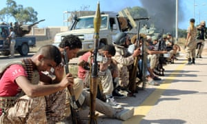 Soldiers from forces aligned with Libya's unity government rest on the road during the assault on Sirte.