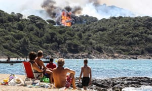 People on the beach look at a forest fire in La Croix-Valmer, near Saint-Tropez