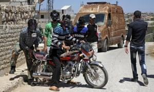 Civilians wear gas masks after a suspected chlorine gas attack on Kansafra village in Idlib province.