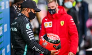 Mick Schumacher presents a helmet belonging to the German's father after Lewis Hamilton equalled Michael's record of 91 race victories.