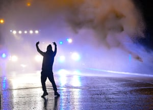 A protestor faces police on Springfield Road