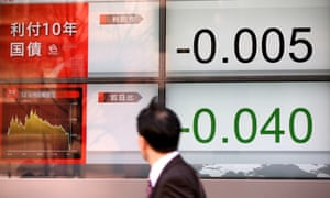 A commuter passes an electric display as the Japanese government's 10-year bond turns negative for the first time last month.