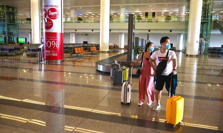 Passengers with facemasks in the empty arrival hall of Noi Bai International Airport in Hanoi.