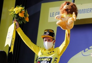 Primoz Roglic, wearing the overall leader's yellow jersey, celebrates on the podium.
